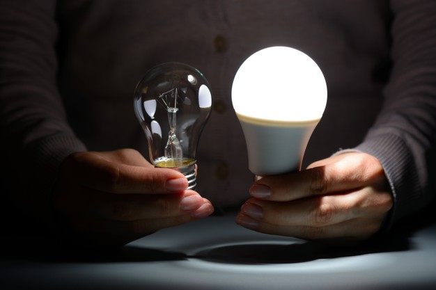 female-hands-holding-glowing-led-incandescent-bulbs-dark_168730-1029